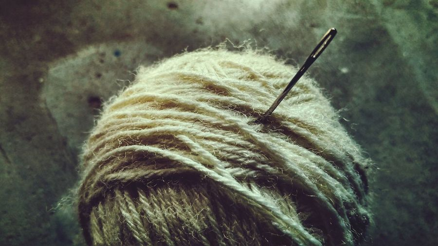 Close-Up Of Sewing Needle In Wool On Table