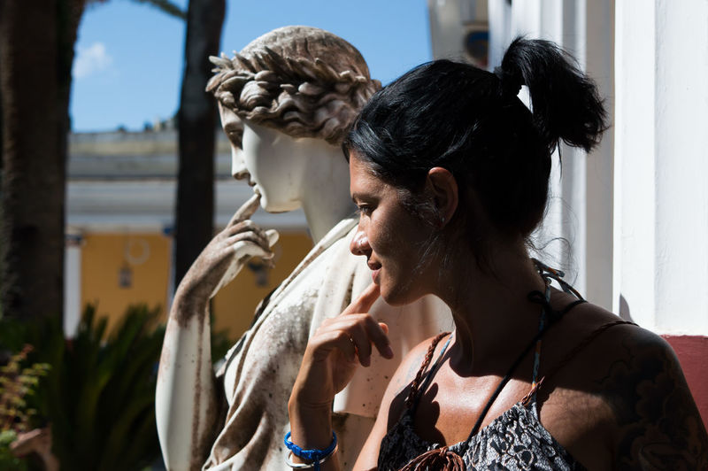 Side View Of Woman Imitating Statue In City