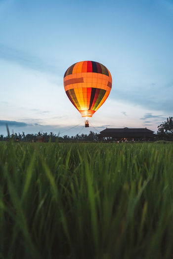 Hot air balloon on field against sky
