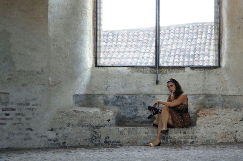 Portrait of girl sitting on window