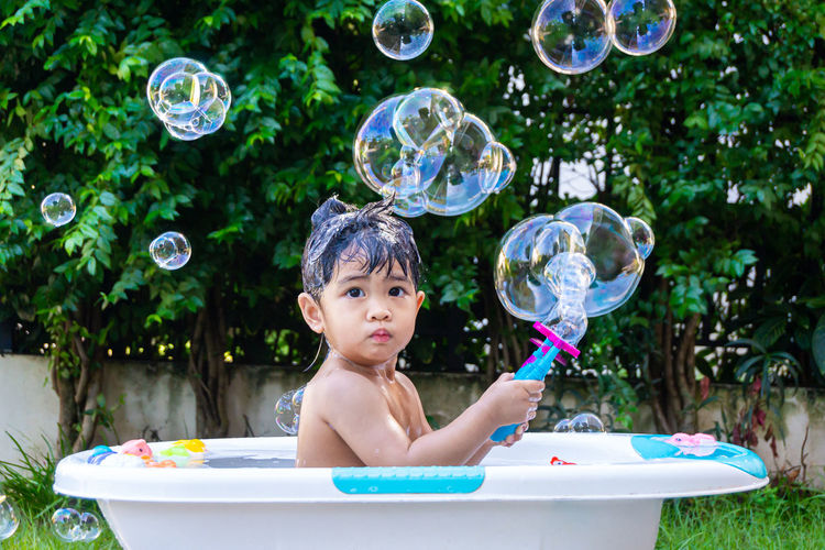Portrait of smiling boy with bubbles in bathtub at yard