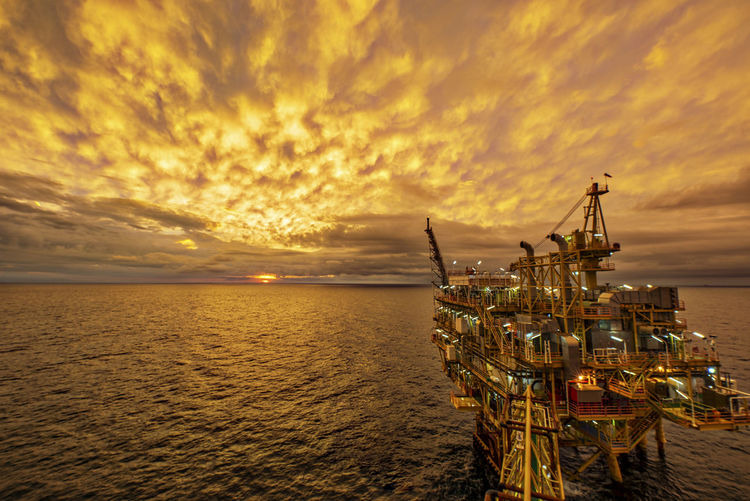 Offshore platform in sea against cloudy sky during sunset