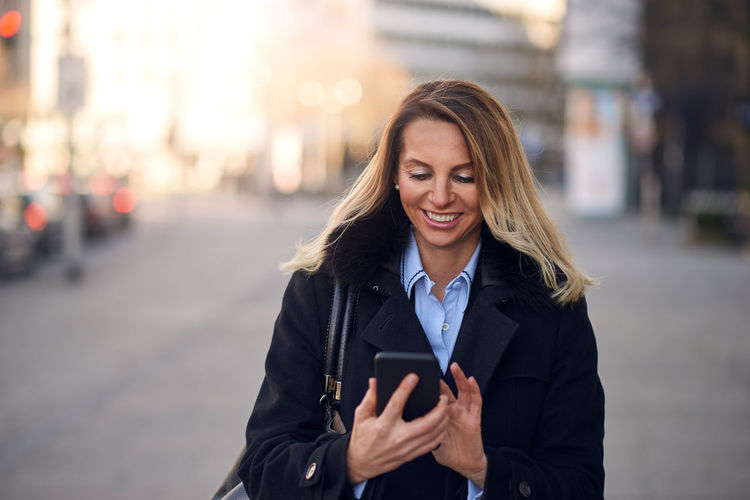 Smiling mature businesswoman using mobile phone while standing on street