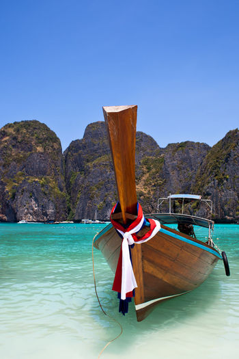 Boat on turquoise sea - Maya Bay - Thailand Bay Beach Blue Clear Sky Copy Space Landscapes With WhiteWall Leisure Activity Lifestyles Mountain Nature S Scenics Tranquil Scene Tranquility Vacations Water Waterfront
