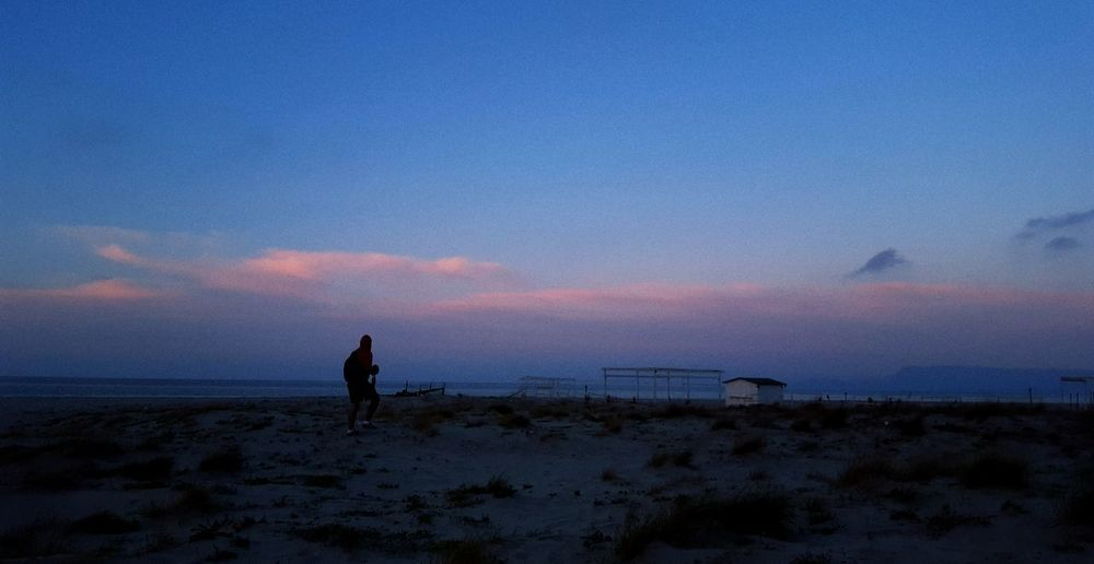 Rear view of silhouette man standing on beach during sunset