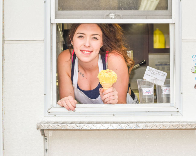 Young girl serving ice cream Adult Cheerful Day Eating Employment Food Food And Drink Front View Happiness Holding Ice Cream One Person One Young Woman Only Outdoors Part Time Job People Portrait Real People Smiling Student Summer Job Summer Views Sweet Food Young Adult Young Women
