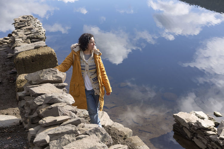 High angle view of young woman standing on rock against lake with reflection of sky