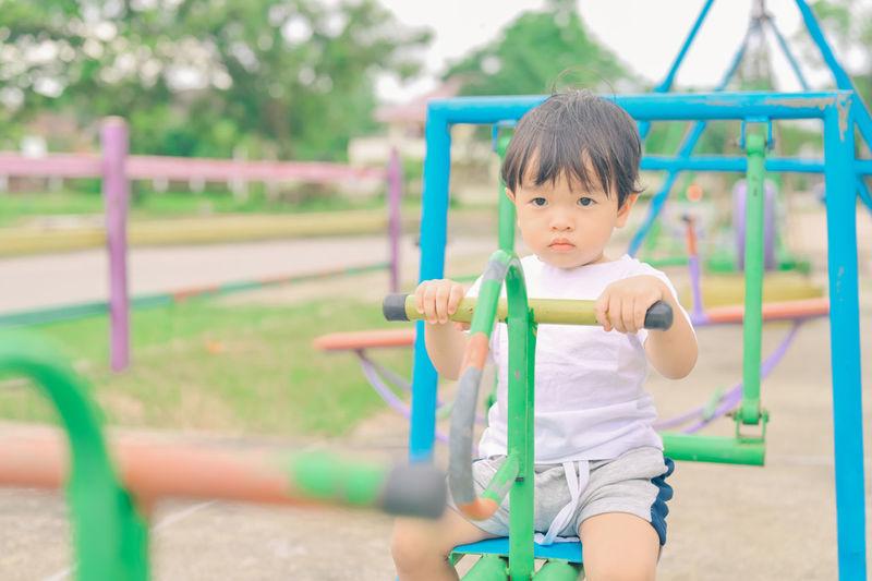 Portrait of cute boy playing on field