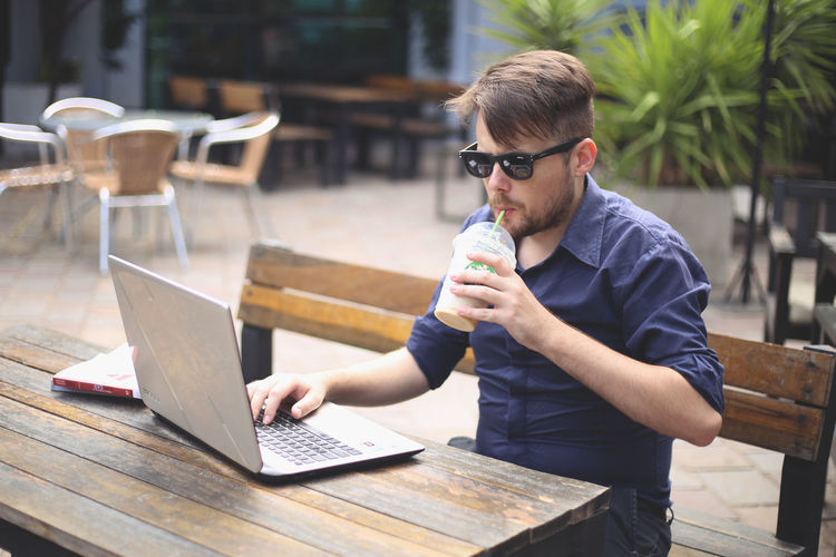 Glasses One Person Wireless Technology Real People Communication Laptop Business Casual Clothing Cafe Lifestyles Using Laptop Cup Adult Entrepreneur Starbucks Coffee Coffee Sunglasses Chic Young Men Business Young Entrepreneur Cafeteria