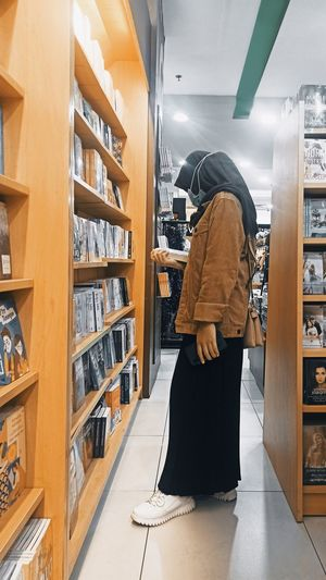 Side view of woman standing at book shop