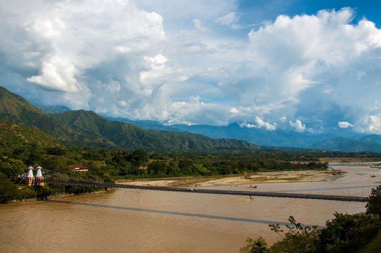 A large bridge spanning the Cauca River Antioquia Attraction Cars Cauca Colombia Countryside Day Engineering Lake Landmark Landscape Mountain Nature Outdoors River Santa Fe Scenics Spanning Structure Tourism Transportation Travel Water Waterfront West