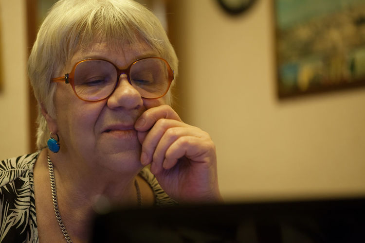 Close-Up Of Senior Woman Using Laptop At Home