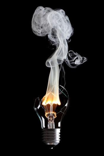 Close-Up Of Burning Light Bulb Against Black Background