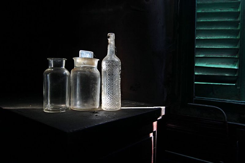 Close-up of bottles on table in darkroom