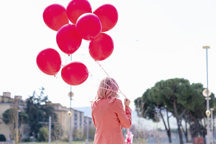 Rear view of woman standing with pink balloons against sky