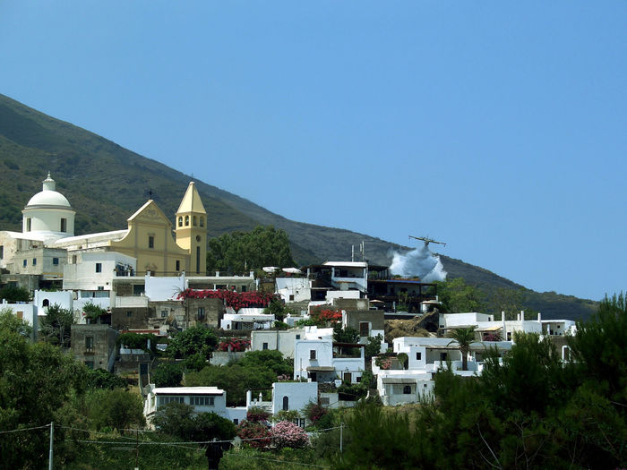 Aircraft over houses against clear sky at aeolian islands
