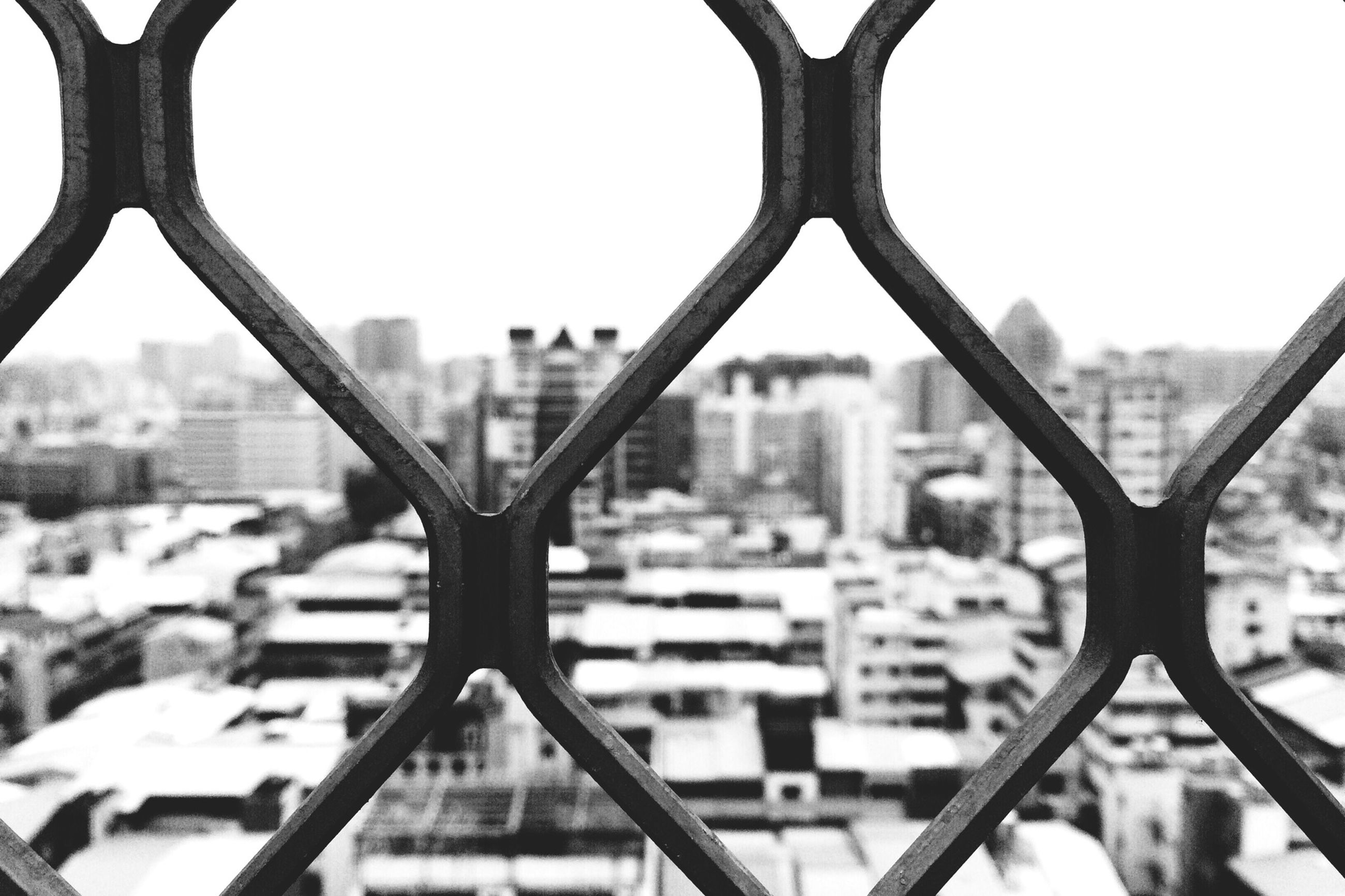 metal, focus on foreground, architecture, built structure, city, cityscape, chainlink fence, clear sky, building exterior, river, close-up, fence, protection, sky, railing, metallic, safety, day, water, connection
