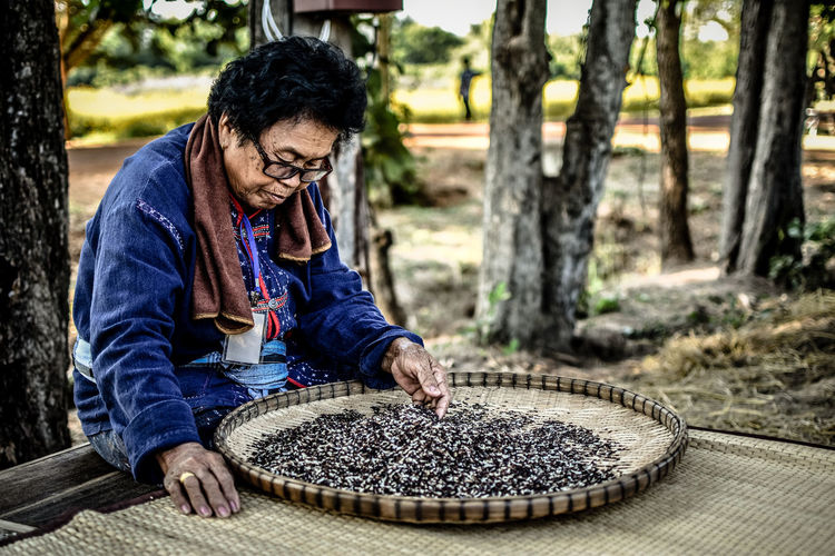 Woman wearing hat sorting rice against trees