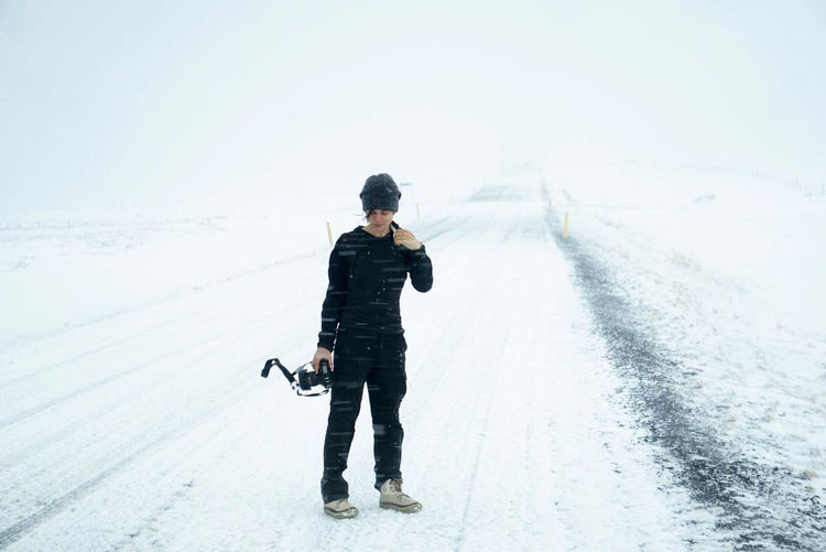 Full length of man standing on road during winter