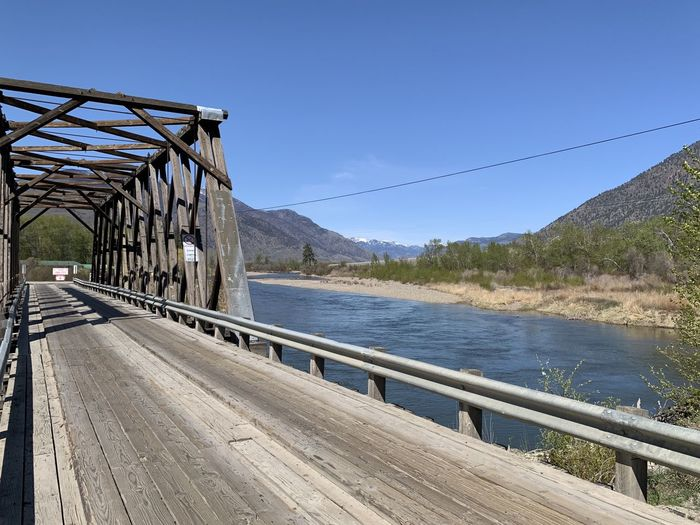 Footbridge over mountains against clear blue sky