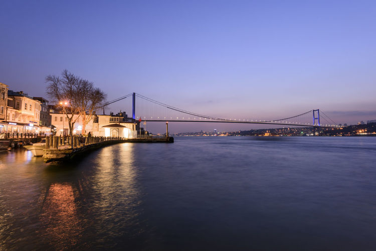 Illuminated suspension bridge over river against clear sky