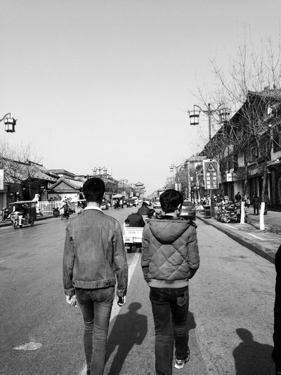 China City Clear Sky Day Friends Leisure Lifestyles Men Nature Outdoors People Real People Rear View Road Sky Standing The Way Forward Togetherness Two People Walking
