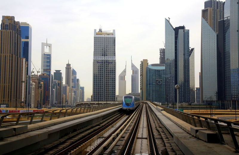 View of dubai skyscrapers and a running train from the subway track