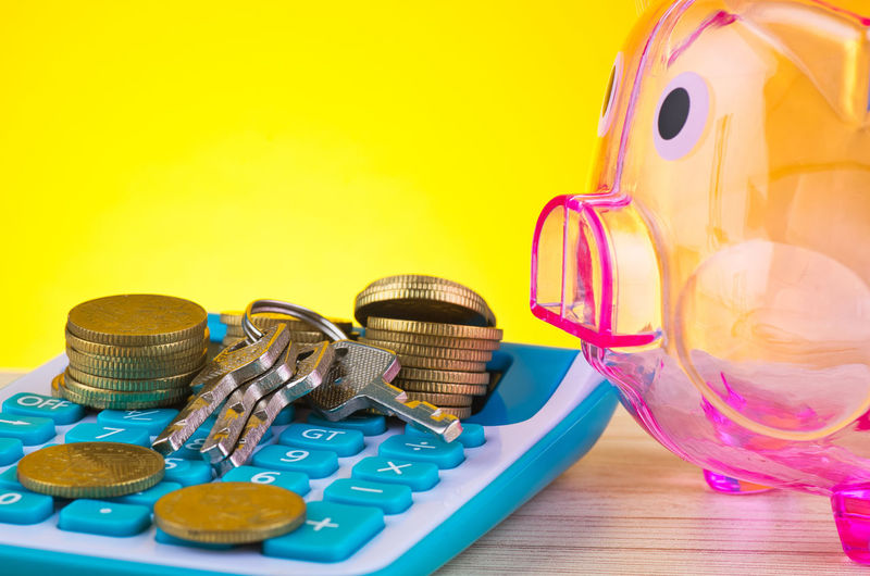 empty piggy bank, stacking coin with bunch of key on calculator Still Life Table Indoors  No People Container Large Group Of Objects Coin Jar Glass - Material Yellow Colored Background Close-up Transparent Choice Variation Multi Colored Lid Food And Drink Metal Studio Shot Glass