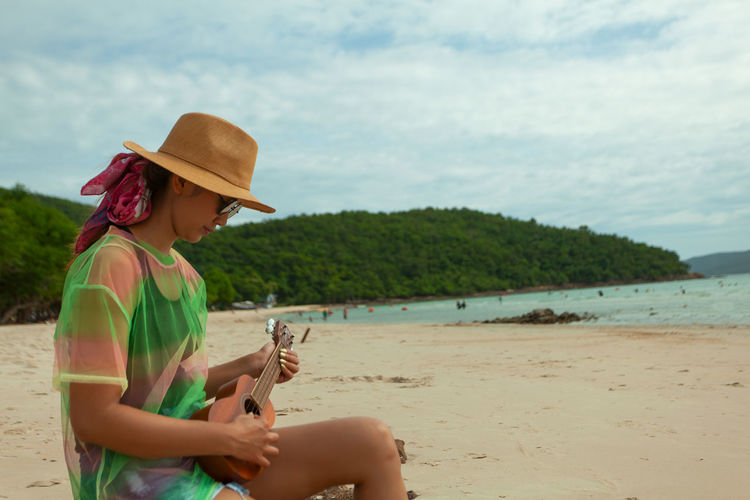Woman playing ukulele while sitting at beach against sky