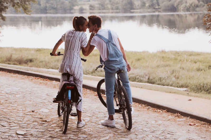 Rear view of couple walking on bicycle