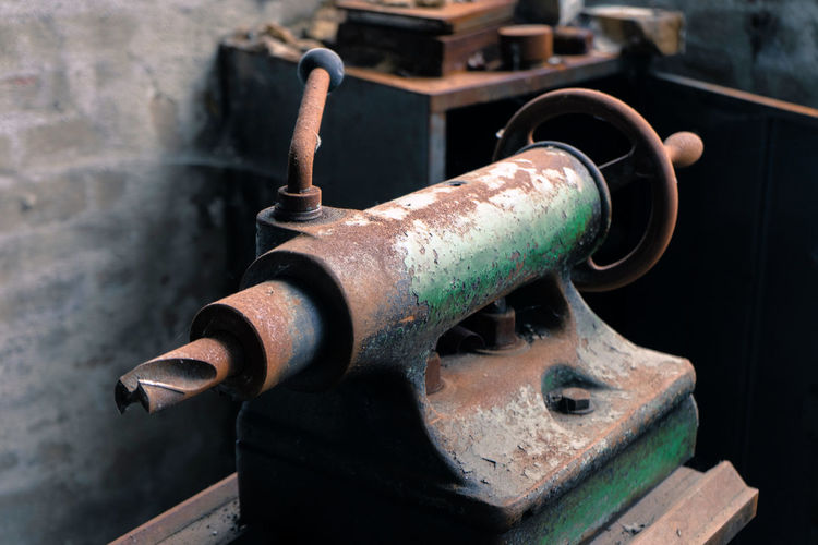 Detail of an ancient rusted and oily lathe in an abandoned industrial hall