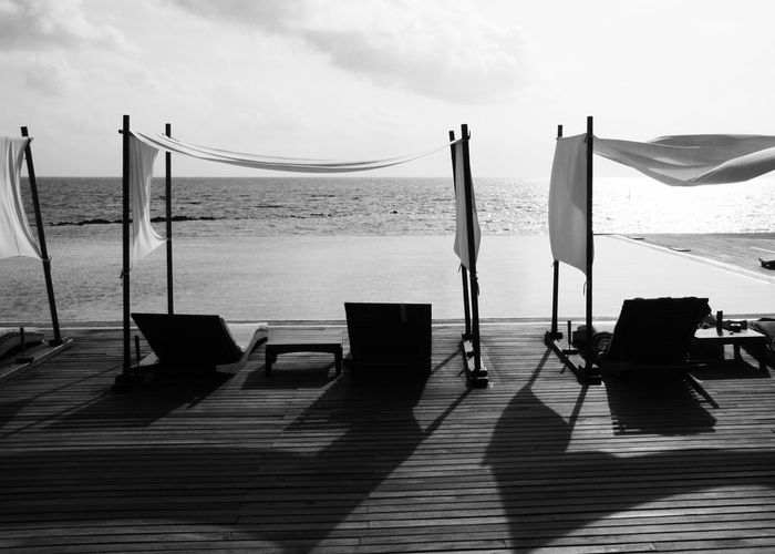 scenic view of deck chairs by infinity pool and sea Absence Architecture Beach Beauty In Nature Black And White Deck Chairs Holiday Horizon Over Water Infinity Pool Light Light And Shadow Maldives Nature Nature Outdoors Parasol Reflection Scenics Sea Shadow Sky Swimming Pool Travel Water The Great Outdoors - 2017 EyeEm Awards Been There. Connected By Travel Modern Hospitality