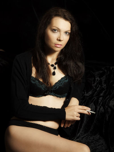 Portrait Of Sensuous Woman With Cigarette Sitting On Bed At Home
