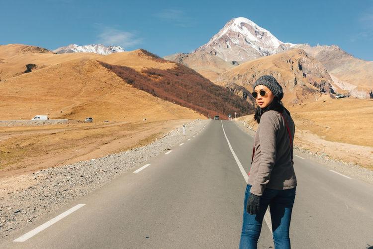 Man standing on road against mountain range