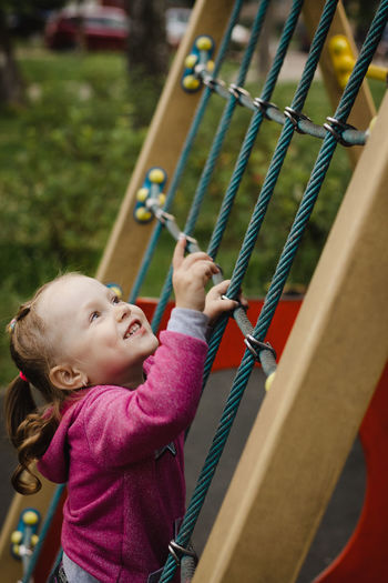 Low angle view of girl holding rope in playground