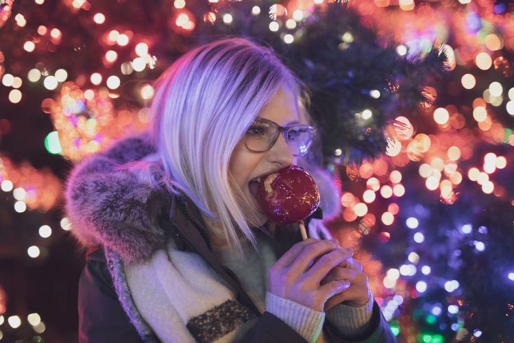Young woman eating caramelized apple during christmas at night