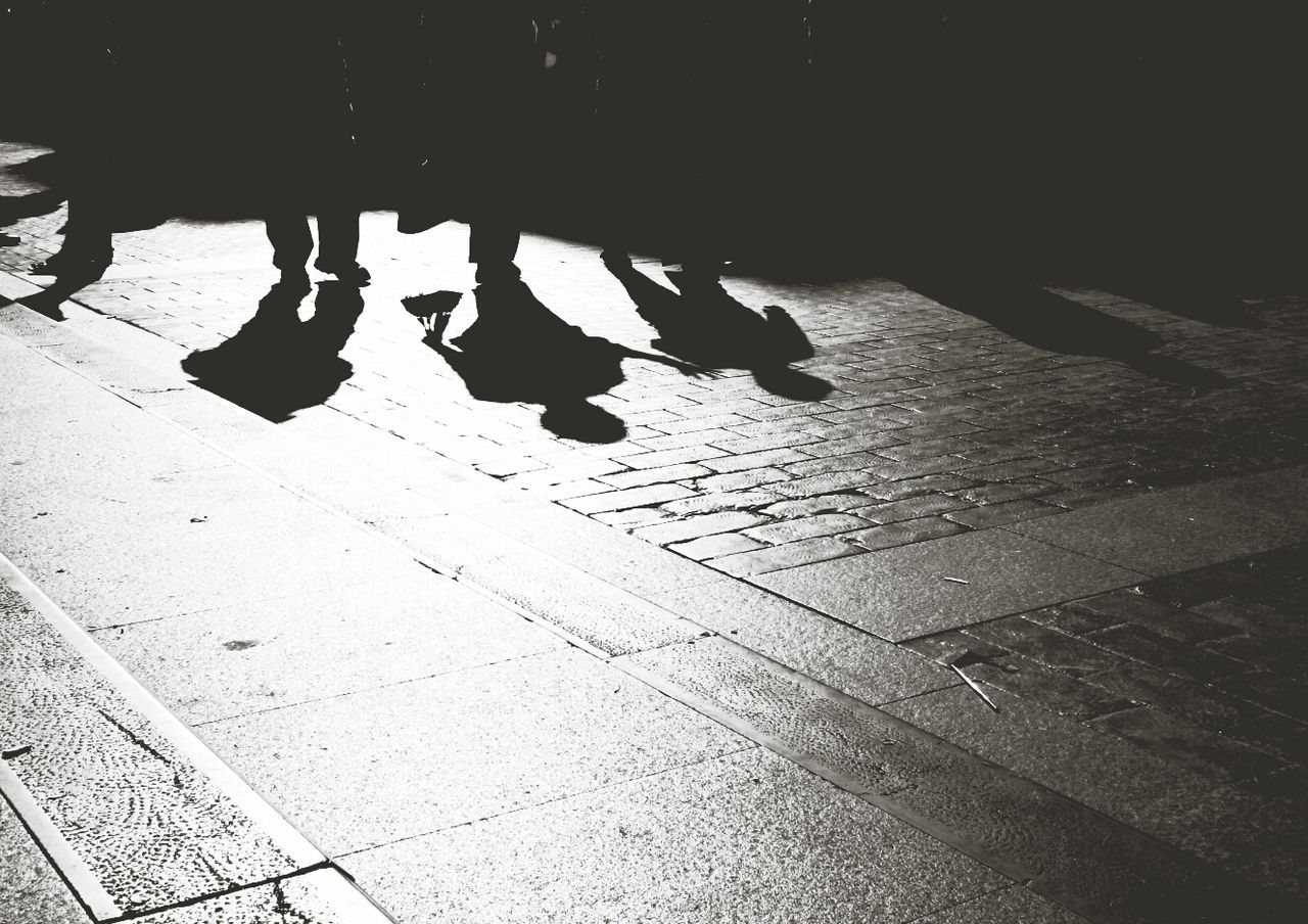 Low Section Of Silhouette People Walking On Street During Sunny Day
