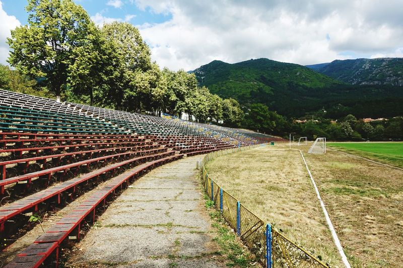 Bulgarian football grandstand in the countryside Bulgarian Soccer Grandstand Football Stadium Football Ground Plant Sky Cloud - Sky Day Nature Tree Scenics - Nature Mountain Outdoors Field No People Growth Tranquility