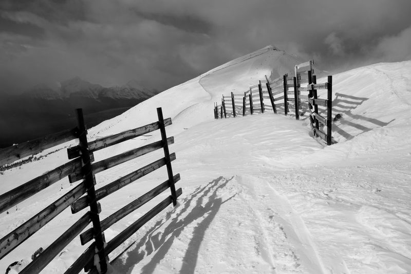 High Angle View Of Fence On Snowcapped Mountains Against Sky During Sunny Day
