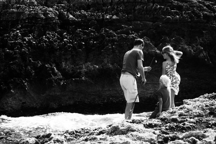 Family By Stream In Sunny Day