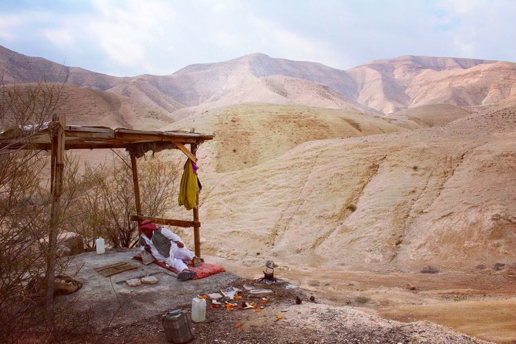 Man Relaxing On Landscape Against Mountains