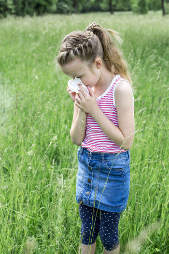 Girl sneezing while standing on field