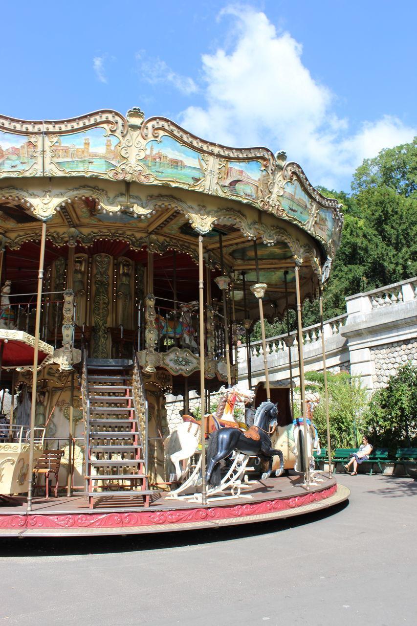 amusement park, amusement park ride, real people, sky, day, carousel, leisure activity, arts culture and entertainment, outdoors, built structure, carousel horses, cloud - sky, men, architecture, large group of people, building exterior, nautical vessel, people