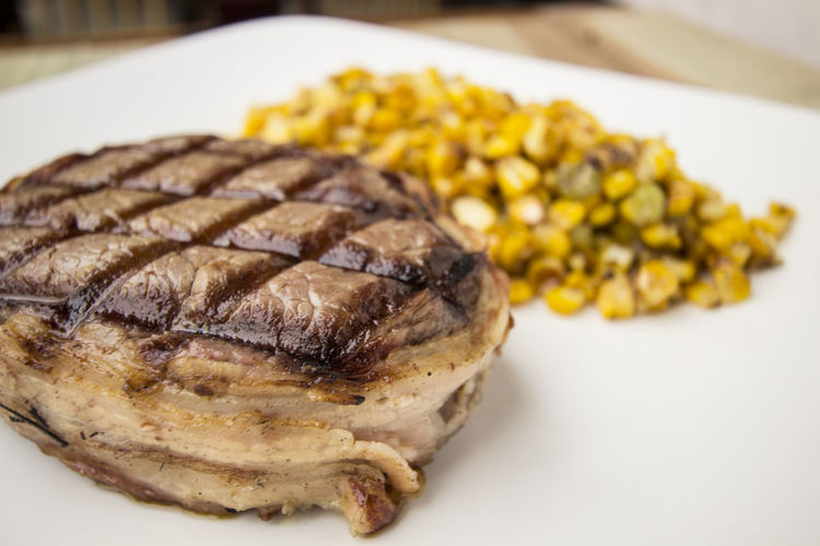 Close-up of grilled tuna with sweetcorns in plate on table