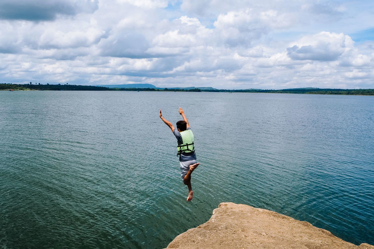 Rear view of man jumping in sea against sky