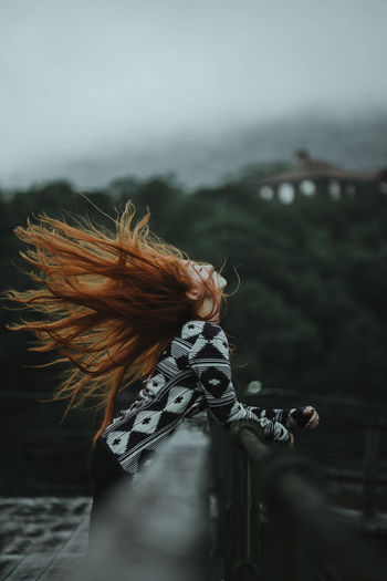 Side view of redhead woman tossing hair while leaning on railing