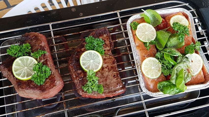 Steaks and salmon next to each other on a grill . ... Salmon Dinner Steak Dinner Steaks Steak Herb High Angle View Healthy Lifestyle Vegetable Preparation  Close-up Food And Drink Plant Green Color Metal Grate Basil Barbecue Grill Barbecue Grilled Lemon