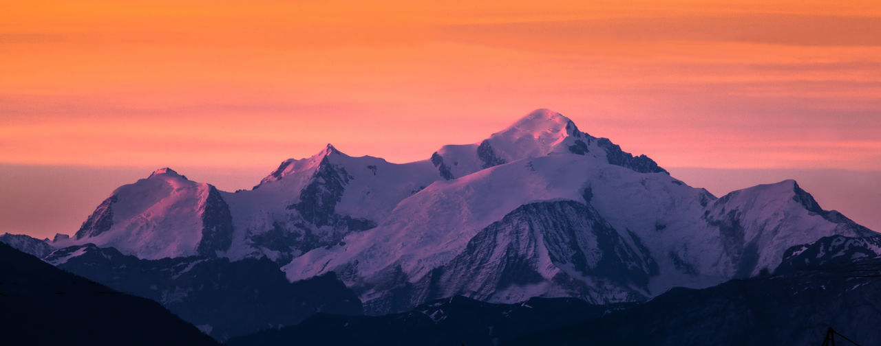 Scenic view of snowcapped mountains during sunset