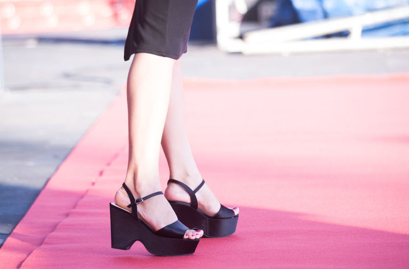 Low section of woman wearing high heels standing on red carpet