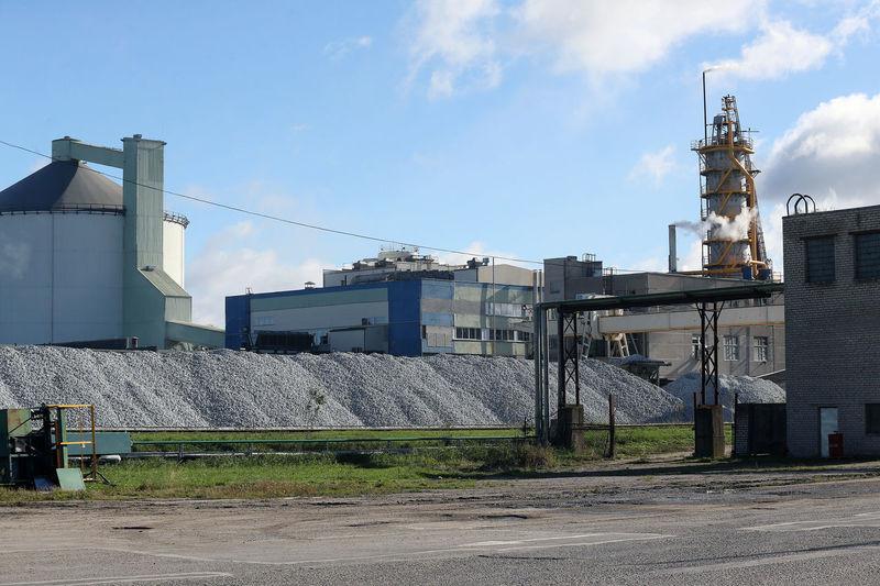 Factory by buildings against sky